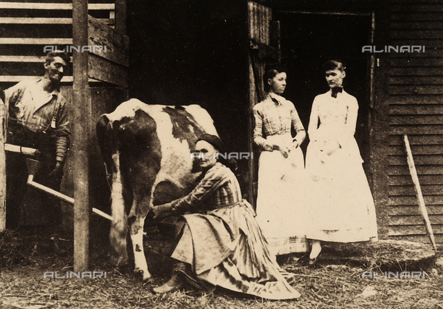 Portrait of a farmer as she milks a cow. Next to the woman are her husband and two daughters.
