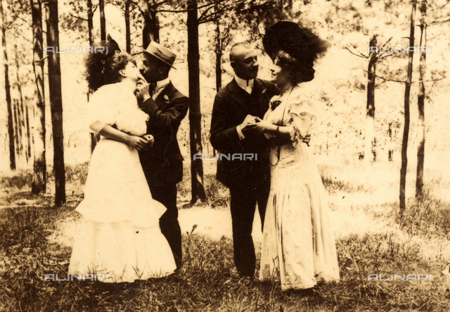 Two young couples embracing in a pinewood.