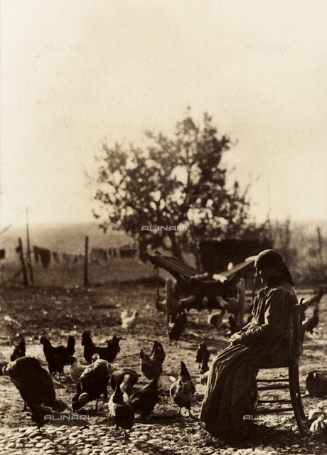 An ederly woman seated on a chair in a farmyard, surrounded by chickens.