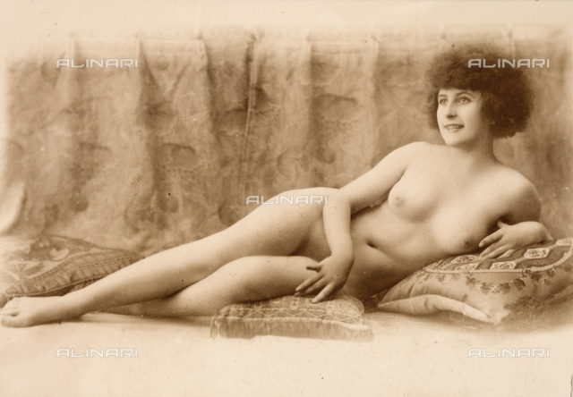Full-length nude portrait of a young woman lying on the floor, propped up on cushions.