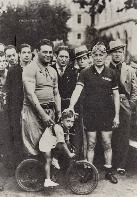 Two cyclist pose with a little boy riding a small bike; behind them, a group of men.