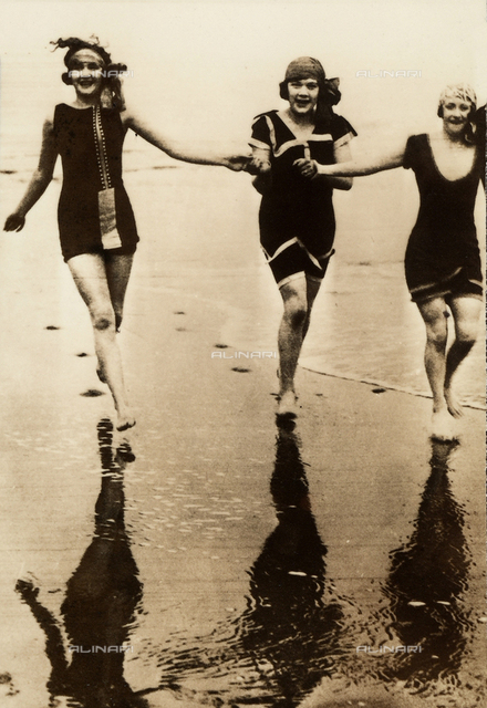 Three young women in bathing suits run along the water's edge of a beach.