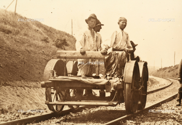 Men travelling on a railroad trolley.