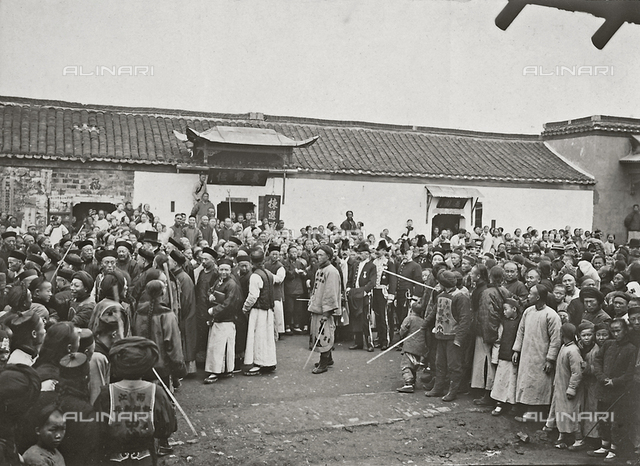 A crowd of people observing a demonstration in a Chinese city