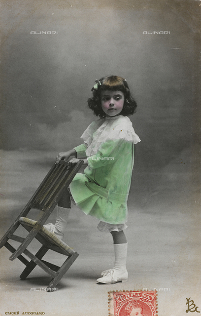 "Postcard depicting a little girl posing in a studio with a chair, ""Album para Tarjetas postales"""