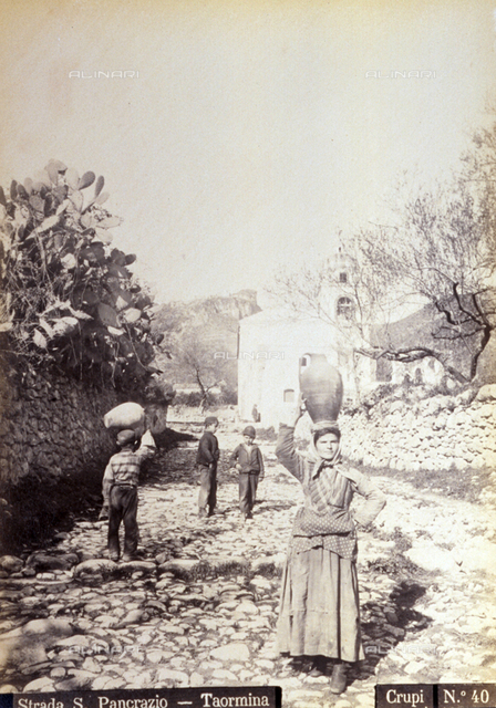 The characteristic Via San Pancrazio in Taormina. In the foreground a working class woman is carrying an amphora on her head. At the center of the picture three little boys