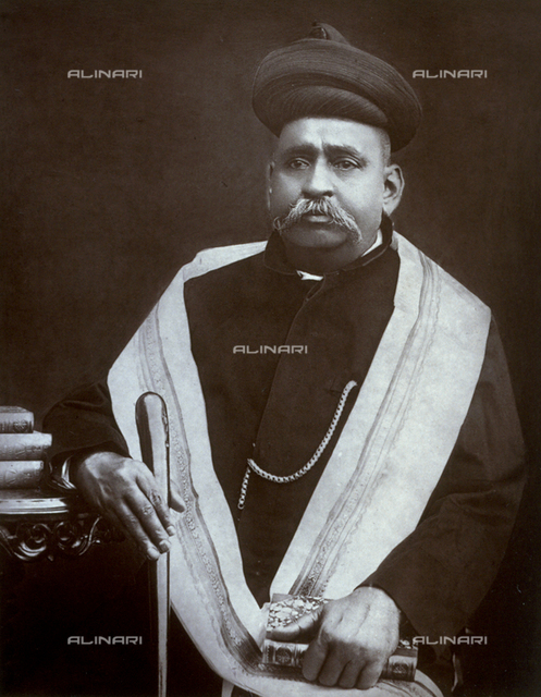 Three-quarter-length portrait of the Prime Minister of Baroda Laxuman Jagannath in austere ethnic clothes. He is sitting and holding a book and a cane