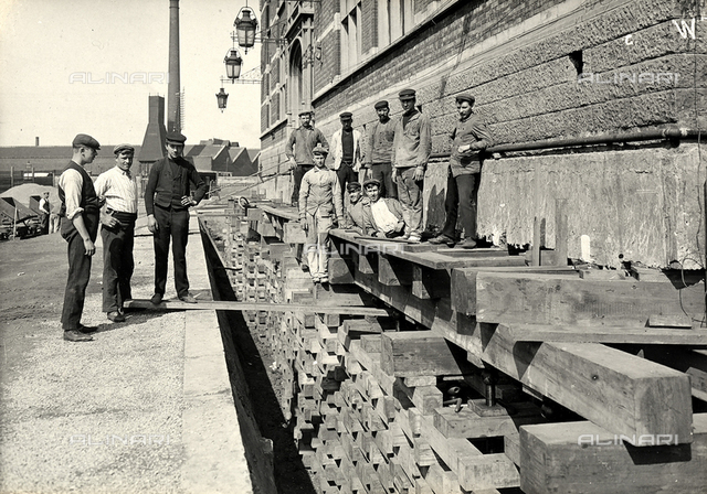 A group of workers photographed outside the Dam railway station in Anvers, during preparation work for the installment of tracks used in the moving operations of the structure.