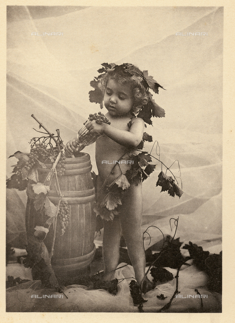 Portrait of a child among leaves and bunches of grapes like Bacchus, next to wine cask
