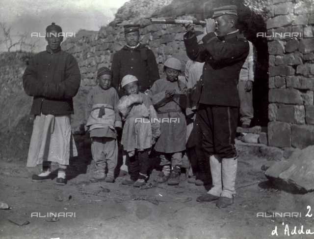 Chinese Manchurian man, in traditional attire, shown in a street with a few children and two men in uniform. On the right men in uniform are looking through a spyglass