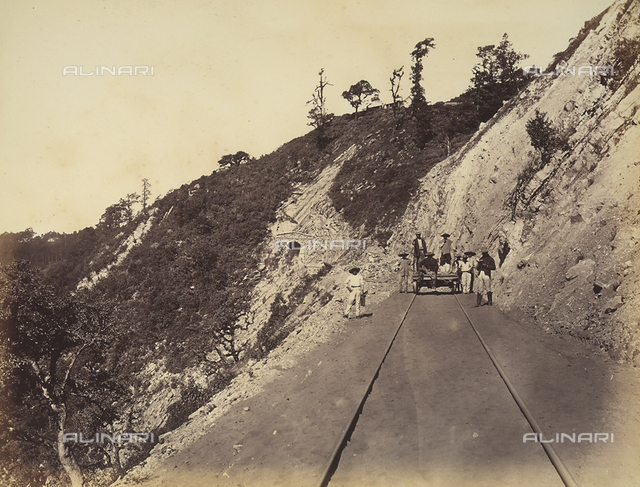 """A group of men with a trolley on a railroad track in Mexico. In the background, the entrance to the tunnel number 16 """"Boca del Monte""""."""