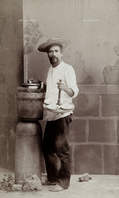 Prtrait of a Mexican street vendor. The man is holding a bowl and a few plates.