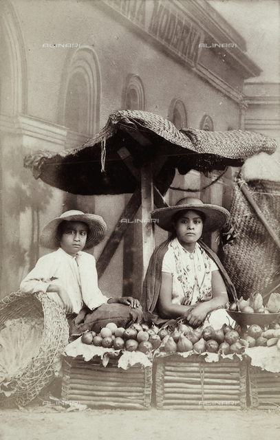 Portrait of a young Mexican couple, fruit vendors, in traditional dress.