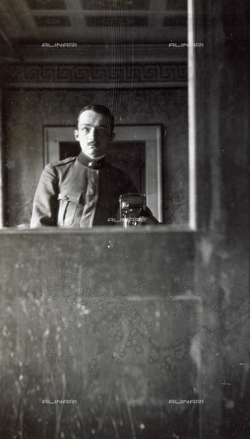 Young soldier photographing his reflection in a mirror