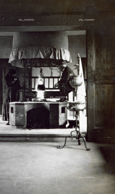 The kitchen of Villa Frangipane near Pavia di Udine. At the center of the picture a man is warming himself at the large circular fireplace while an elderly woman is blowing through a long tube to revive the fire