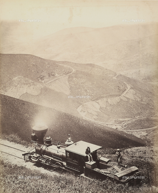 Steam locomotive travelling in the Peruvian mountains. Below, the curves of a winding road on the slope of a mountain.