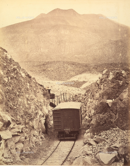 Railroad in the Peruvian mountains: a wagon on a track squeezed between two faces of rock.
