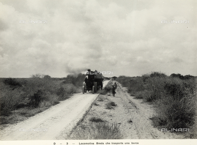 A Breda locomotive transporting a boat along a path in Somalia. Photograph commissioned by the Italo-Somalian Agricultural Company