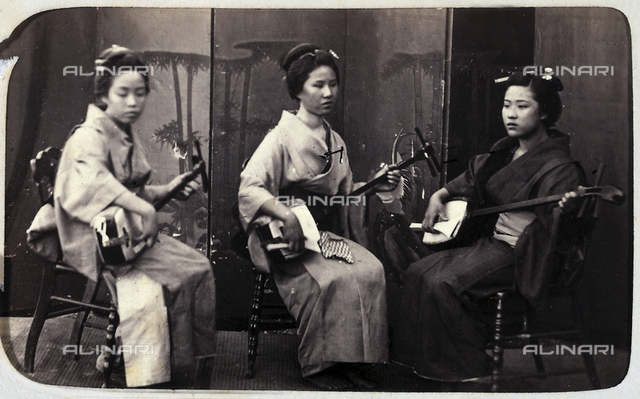 Three young Japanese woman playing a traditional instrument