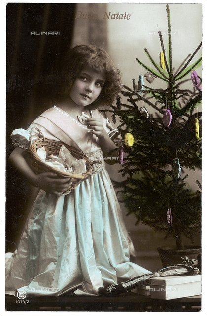 Portrait of a young little girl while eating a cookie and carrying a basket under the Christmas tree, Christmas greeting post-card, with a 'Buon Natale' inscription on the front side and a personal dedication on the back side, the postage stamp indicates the date of 24th of December 1914, Peschiera, Verona, Italy