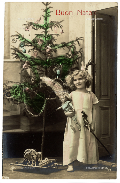 Portrait of a young little girl with her toys near the Christmas tree, Christmas greeting post-card, with a 'Buon Natale' inscription on the front side and a personal dedication on the back side, the postage stamp indicates the date of 19th December 1910 and the city of Ferrara, Italy