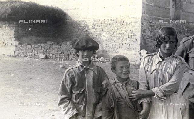 Three-quarter-length portrait of three ragged gypsy children