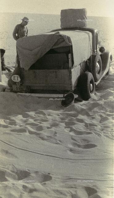 A sand-covered car in the desert, Nigeria