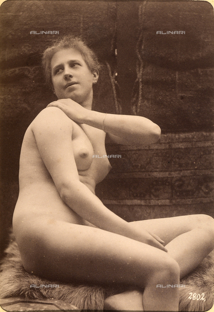 Portrait of a nude woman with a hand on her shoulder