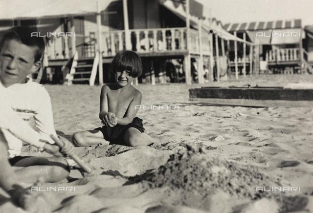 """Two children on the beach in Viareggio; the support contains the indication """"Giggì Botto and Fiamma Pini"""""""
