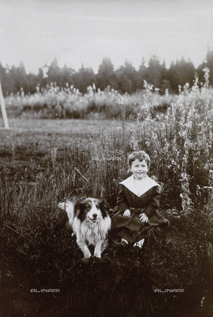 Portrait of a child sitting in a field with his dog (Franz Wolf portrait)