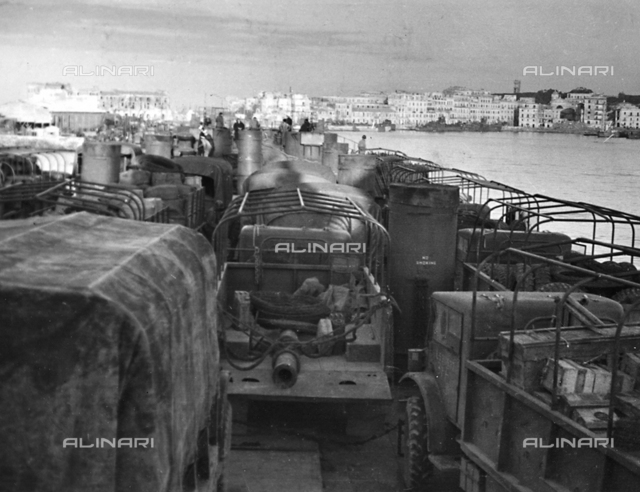 Jeeps being transported on a Navy ship in the Port of Anzio