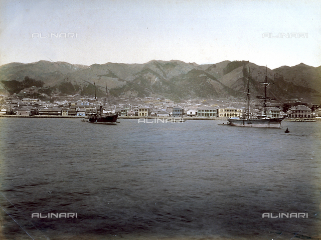 Panorama of the port of Kobe, in the gulf of Osaka, in Japan. In the foreground boats tied up, in the background the city set at the foot of the hills