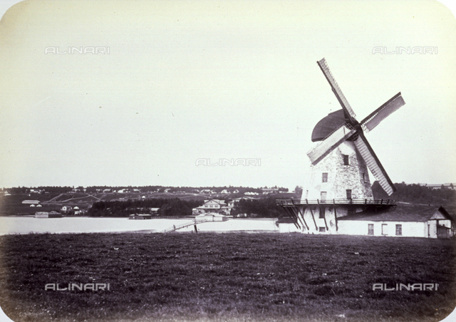 Characteristic windmill near a river, in the environs of Saint Petersburg. In the background panorama of a vast countryside strewn with buildings