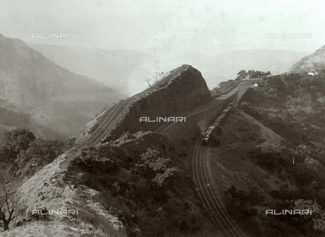 Panoramic view of the terminal railway station of Khandalla. Railroad tracks cut through thhe summit of a mountain; on one track a train is seen leaving the outpost.