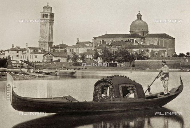 A gondolier in the Venice lagoon, with the Church and the bell tower of San Pietro in Castello in the background
