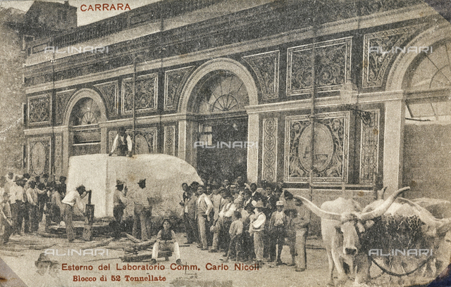 """Carrara - Exterior of the Laboratory of the Comm. Carlo Nicoli, block of 52 tons"": a block of marble transported in the laboratory"