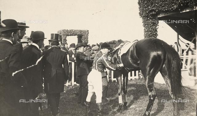 A jockey preparing his horse for a race