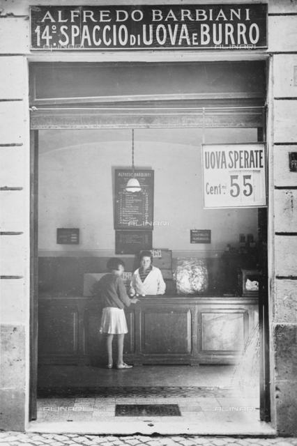 Alfredo Barbiani Firm: shop for the sale of eggs on Via Orfeo in Rome; a clerk and young girl are at the counter.