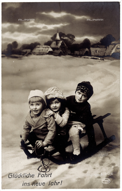 Portrait of a group of children on a sleigh, new year greeting post-card with a 'Glückliche Fahrt ins neue Jahr' inscription on the front side, Germany
