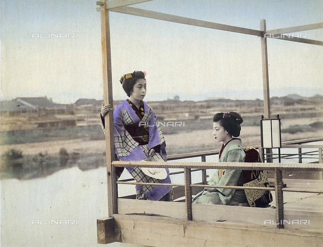 Two geishas wearing kimonos on a terrace