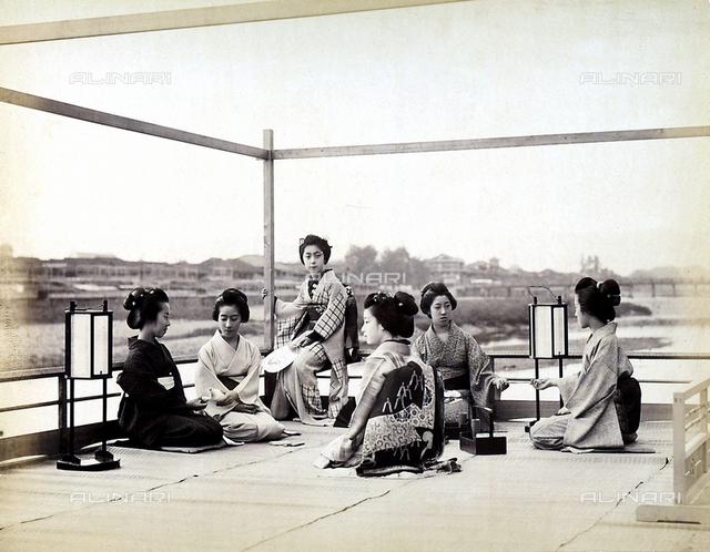 Geishas wearing kimonos on a terrace while serving tea