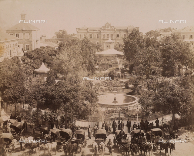 Carriages in front of a park with a fountain