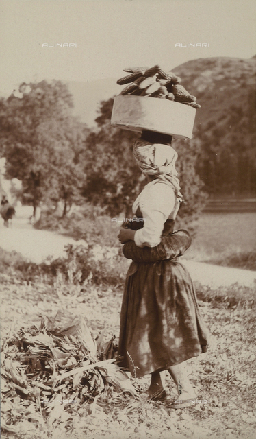 Farming woman with basket of corn-cobs