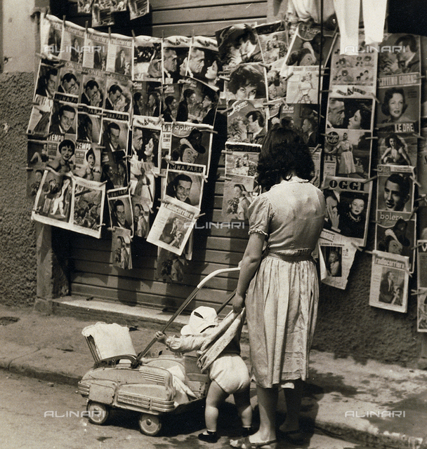 A mother and her child look at magazine covers, Livorno