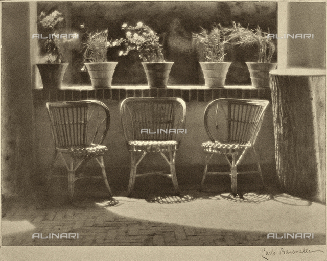 """Windowsill."" Three wicker armchairs lined up on a terrace, some flowering plants are on the sill"