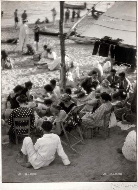 """The evening respite on the beach of Varazze."" Scene of the life of people vacationing at the beach"