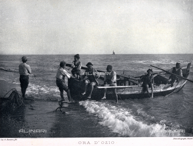 A group of fishermen taking a break on board a boat moored along the sea shore
