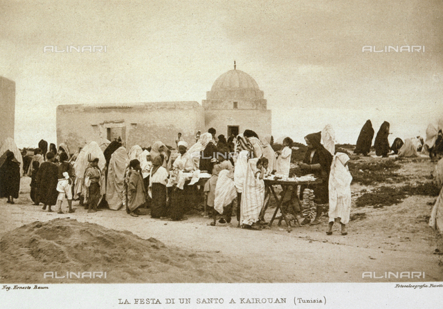 Stalls crowded with people buyering, set out along a road in Kairouan, Tunisia, during a Muslim religious festival