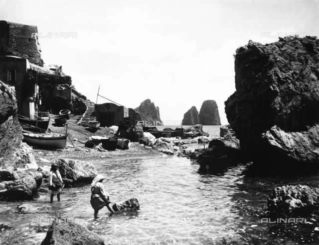 Two women in traditional dress bathing in the waters of Capri, near a small beach on the island. The Faraglioni are in the background