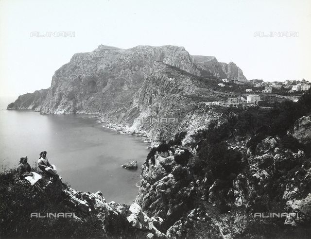 View of Capri. In the foreground, on the left of the photo, two women in traditional dress sitting on the top of a rock.